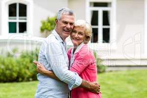 Senior couple embracing outside house at yard