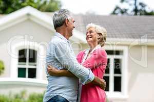 Smiling senior couple against house at yard