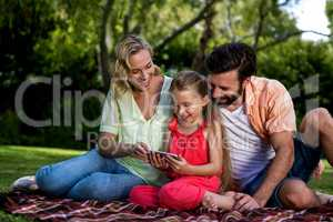Happy parents with daughter looking at mobile phone in yard