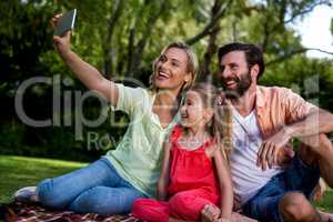 Woman taking selfie with husband and daughter at yard