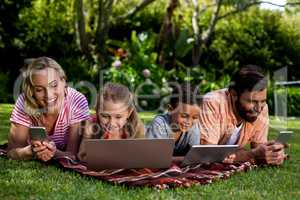 Family using technologies while lying at yard