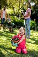 Smiling girl holding flower pot in yard