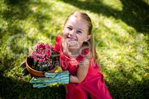 Portrait of smiling girl holding flower pot in yard