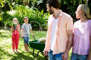 Parents standing with children holding flowerpots in yard