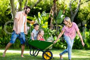 Parents pushing children sitting in wheelbarrow at yard