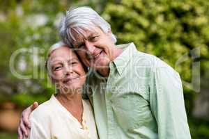 Smiling senior couple standing in yard