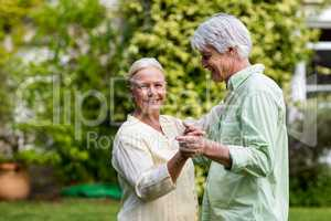 Smiling senior woman with man dancing in yard