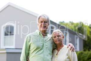 Senior couple standing in yard against house
