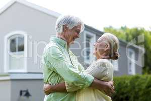 Smiling senior couple embracing in yard