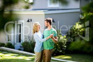 Couple dancing in yard against house