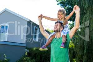 Father carry daughter on shoulders in yard
