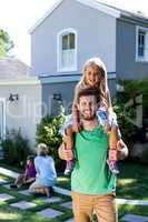 Smiling father carry daughter on shoulders in yard