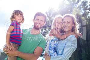 Smiling parent carrying children
