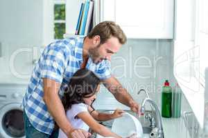 Daughter helping father in washing utensils