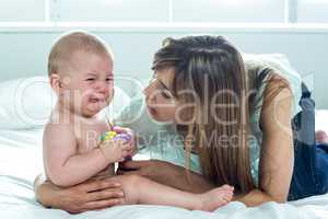 Woman with crying son on bed at home
