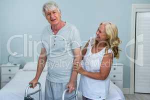 Happy senior woman helping man to walk in bedroom