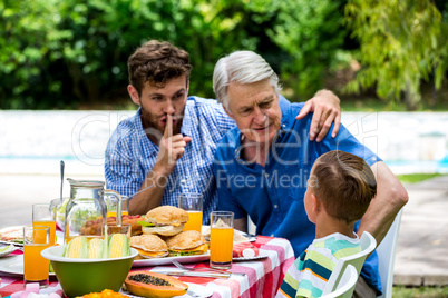Man gesturing silence while son talking with grandfather at lawn