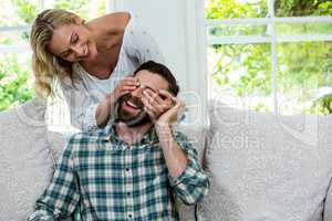 Cheerful wife closing husband eyes from behind