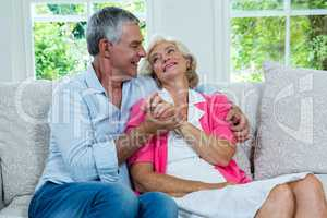Loving senior couple looking at each other in living room