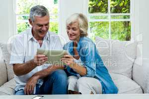 Happy senior couple holding digital tablet in sitting room