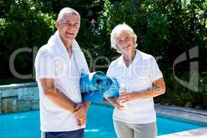 Happy senior couple with exercise mats at poolside