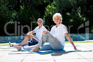 Smiling couple on exercise mat at poolside