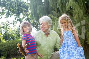Smiling grandfather playing with grandchildren at yard