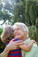 Happy grandfather hugging grandson at yard