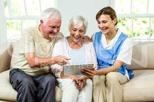 Happy nurse and senior adults holding digital tablet