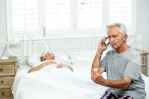 Aged man talking on mobile phone with senior woman relaxing