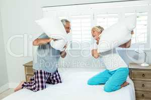 Senior couple playing with pillows on bed