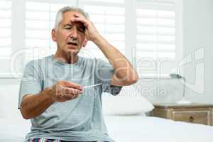 Aged man checking thermometer at home