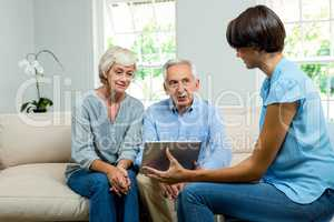 Female consultant showing digital tablet to aged couple at home