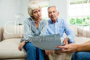 Cropped image of consultant showing report to aged couple