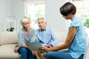 Female consultant showing report to old couple at home