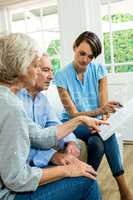 Female consultant reading report with senior couple