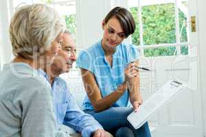 Senior couple reading report with female consultant
