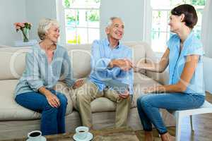 Smiling senior couple with female consultant at home
