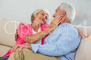 Romantic retired couple sitting on sof