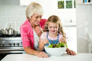 Happy granny and girl preparing vegetables