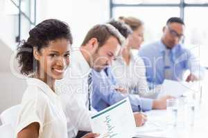 Portrait of businesswoman holding a report at meeting