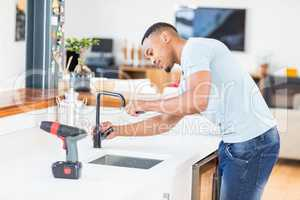 Man tightening tap with a wrench