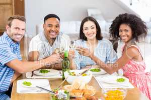 Friends toasting wine glasses while having a meal