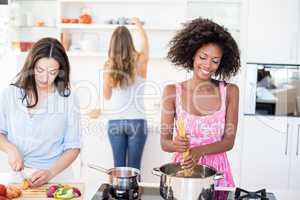 Friends preparing a meal in kitchen