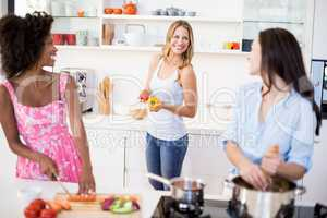Friends interacting while preparing a meal in kitchen