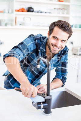 Portrait of happy man fixing tap with tool in the kitchen