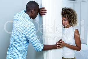Upset couple standing on opposite sides of the wall