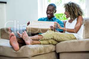 Excited couple sitting on sofa and opening a parcel