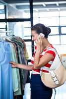Woman talking on mobile phone while shopping for clothes