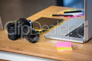 Camera, sticky notes, graphics tablet and laptop at desk